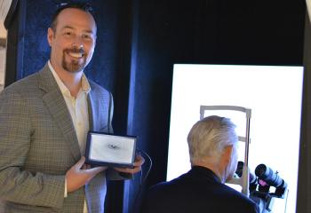 Charles Rutt looks into the glaucoma detection device, Dr. Brennan Eadie displays the image of Charles' eye on a hand-held screen.