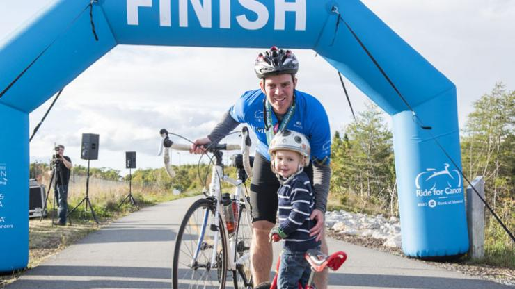 A Ride for Cancer participant hugs his son at the finish line