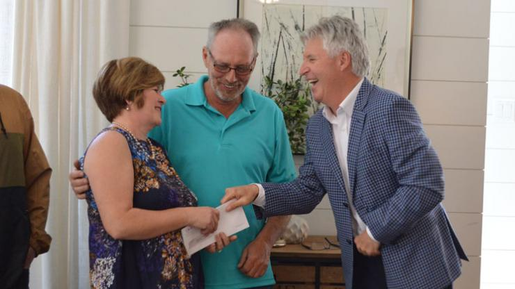 Bill Bean presents a cheque to the QEII Home Lottery winners