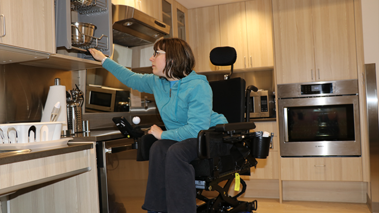 A rehab patient in a wheel chair is adjusting the cupboard height to reach the dishes at the Independent Living Simulation Suites
