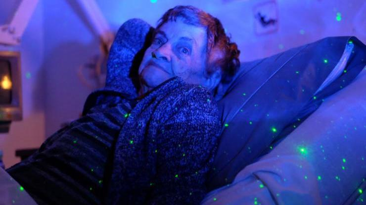 Pictured here is patient Loretta Joyce, enjoying a starlight projector, which helps her relax at night funded by Comfort & Care Grants.