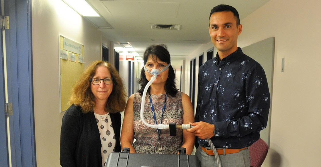 Dr. Debra Morrison and Dr. Hamed Hanafi with the small black sensor attached to the sleep clinic's sleep apnea breathing machine,  modelled by QEII staff Kelmarie Cole