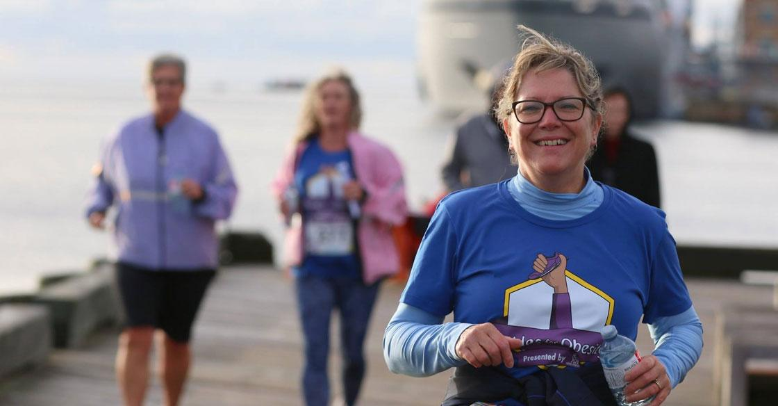 A participant in a QEII Foundation Community Initiative is running on the Halifax boardwalk