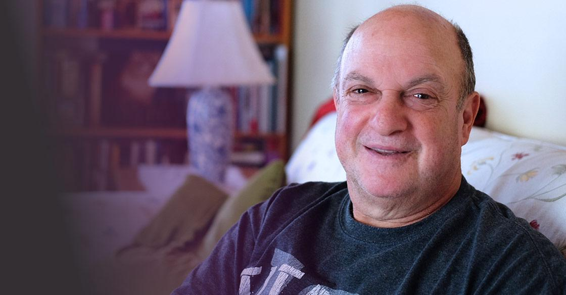 Lorne Abramson, a QEII patient is sitting in his living room.