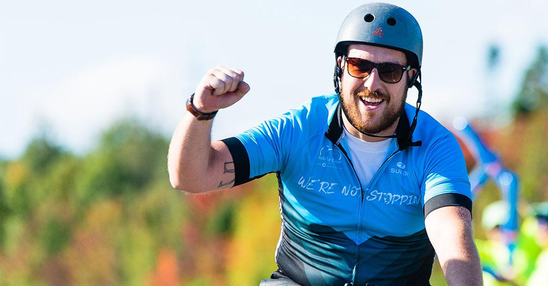 Ride for Cancer participant rides through and finish line and pumps his fist