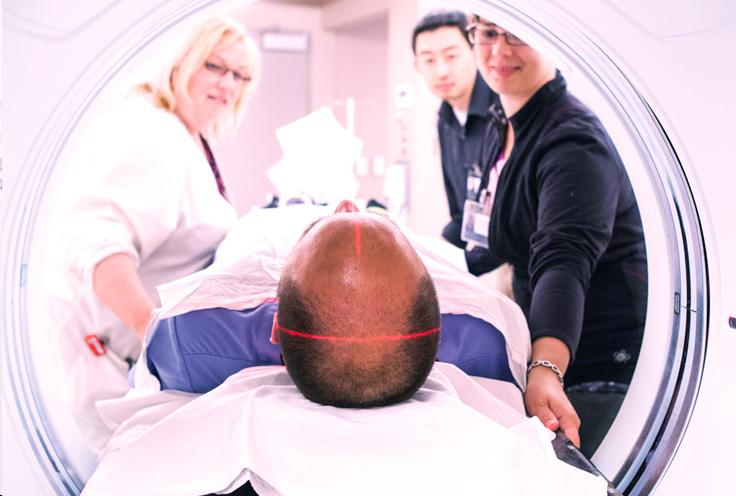 A patient lying down in an MRI machine while three nurses talk to him